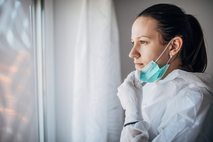 worried doctor looking out the window with gloves and mask on