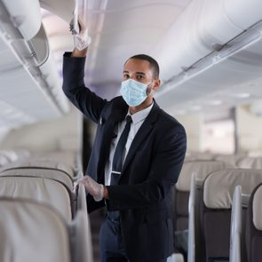 cabin crew on airplane with gloves and mask protection
