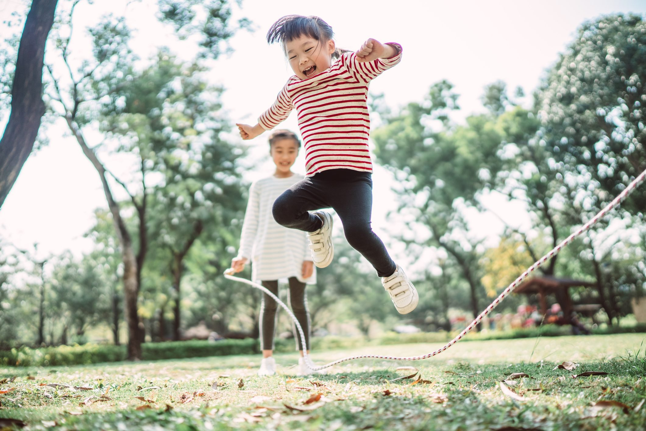 Young family jumping rope joyfully on the lawn