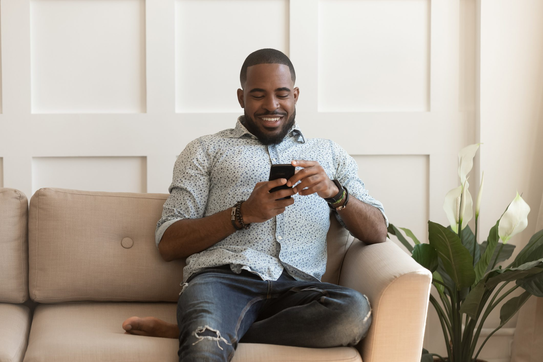 African guy sitting on couch chatting online using smartphone