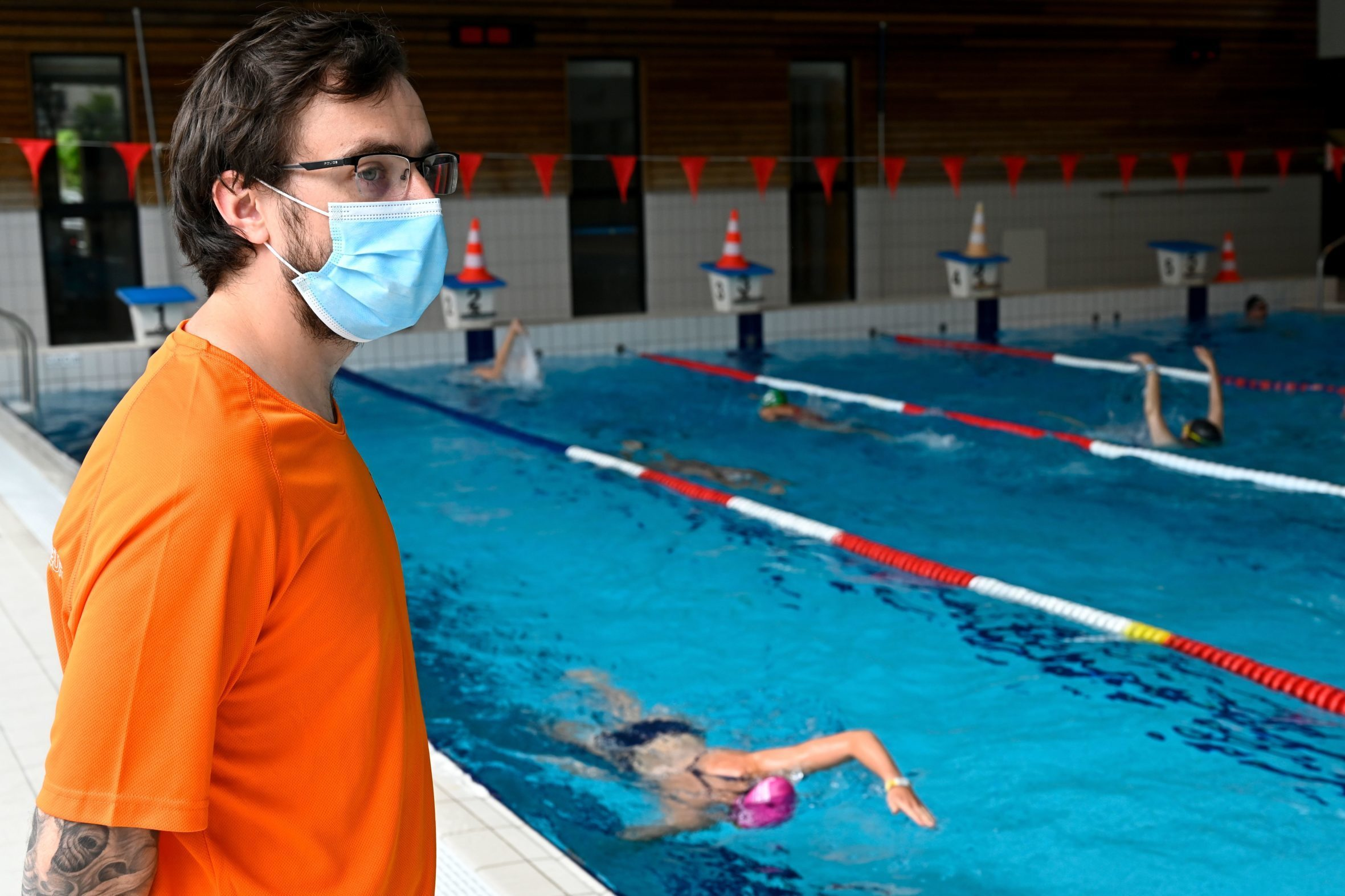 "A lifeguard wearing a protective face mask monitors people swimming in ""La conterie"" public swimming pool in Chartres-de-Bretagne, suburbs of Rennes, western France on June 4, 2020, on the first day of its reopening after a months-long closure aimed at stemming the spread of the COVID-19 pandemic, caused by the novel coronavirus."