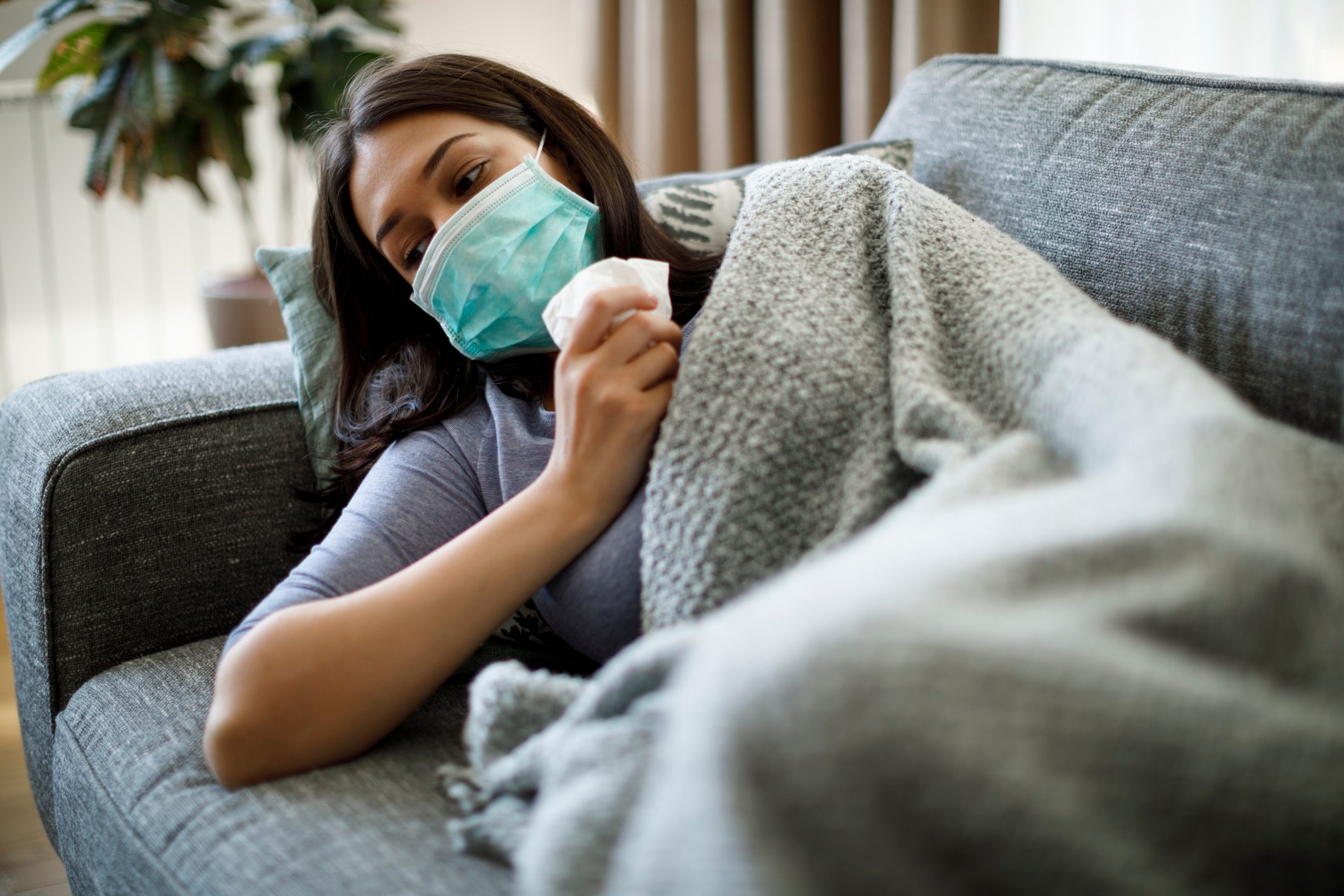 Sick woman with face protective mask lying in bed