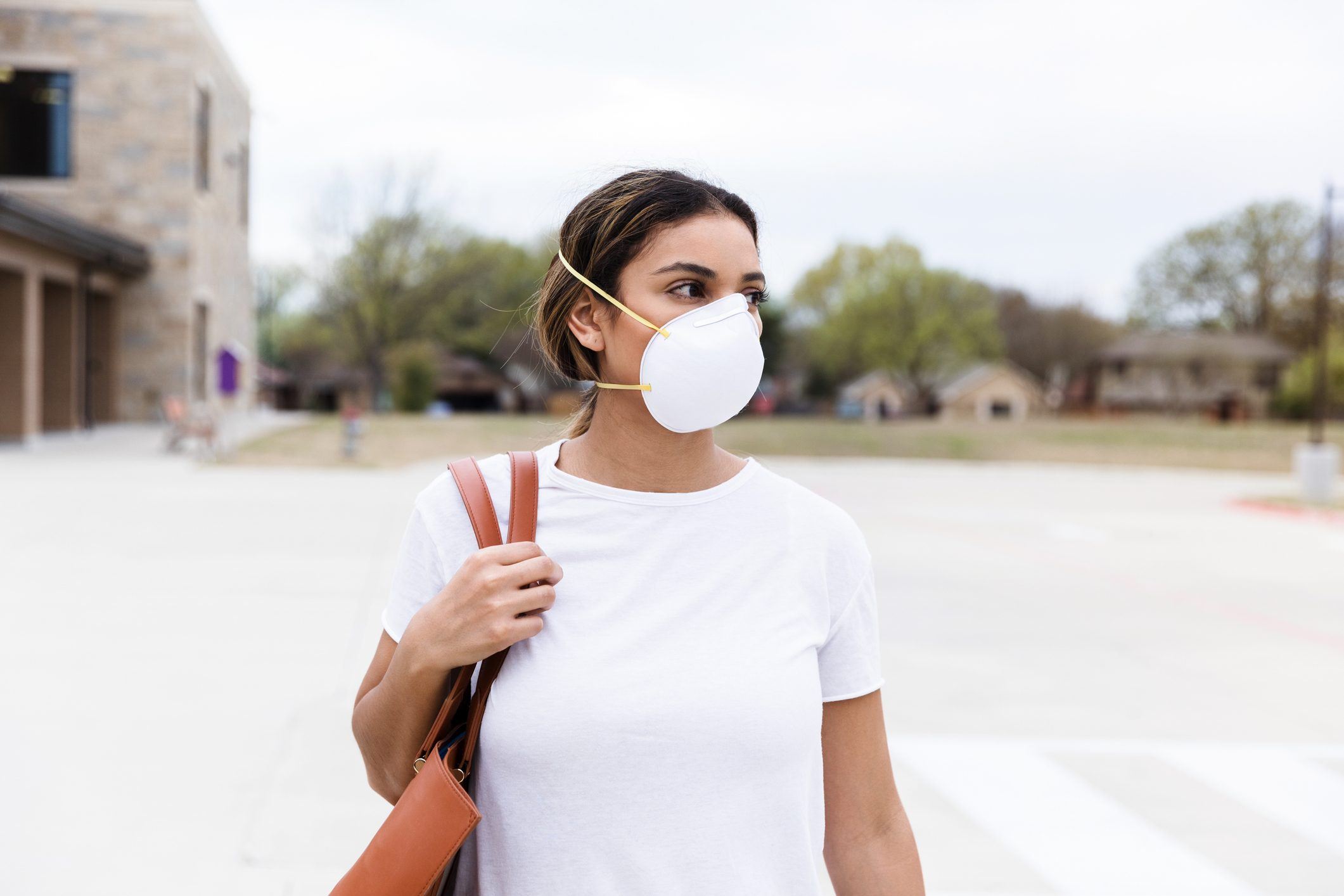 Woman crosses the street wearing an N95 mask