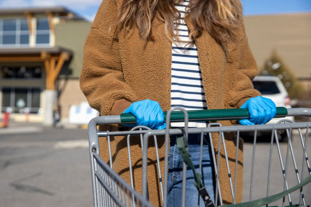 A woman wearing blue latex gloves and pushing a shopping cart during the COVID-19 quarantine.