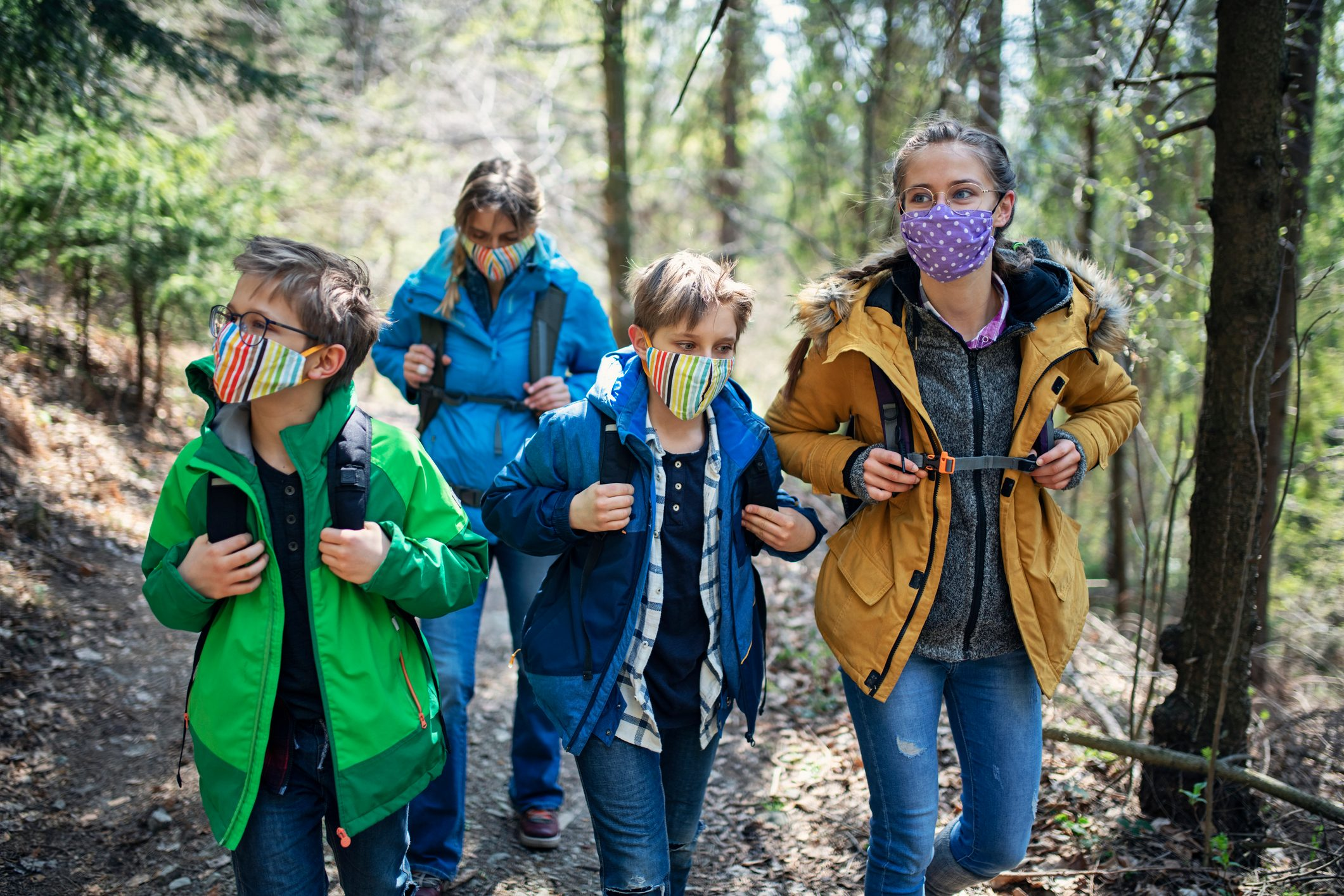Family enjoying hiking in forest during the COVID-19 pandemic