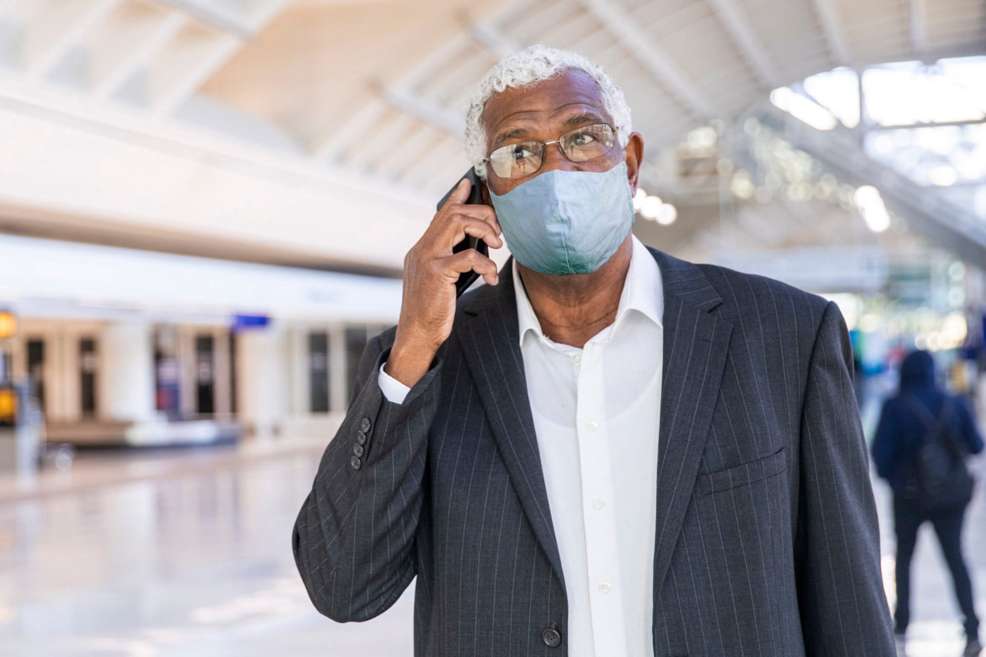 Senior Black Businessman on Phone at the Airport Wearing a Mask