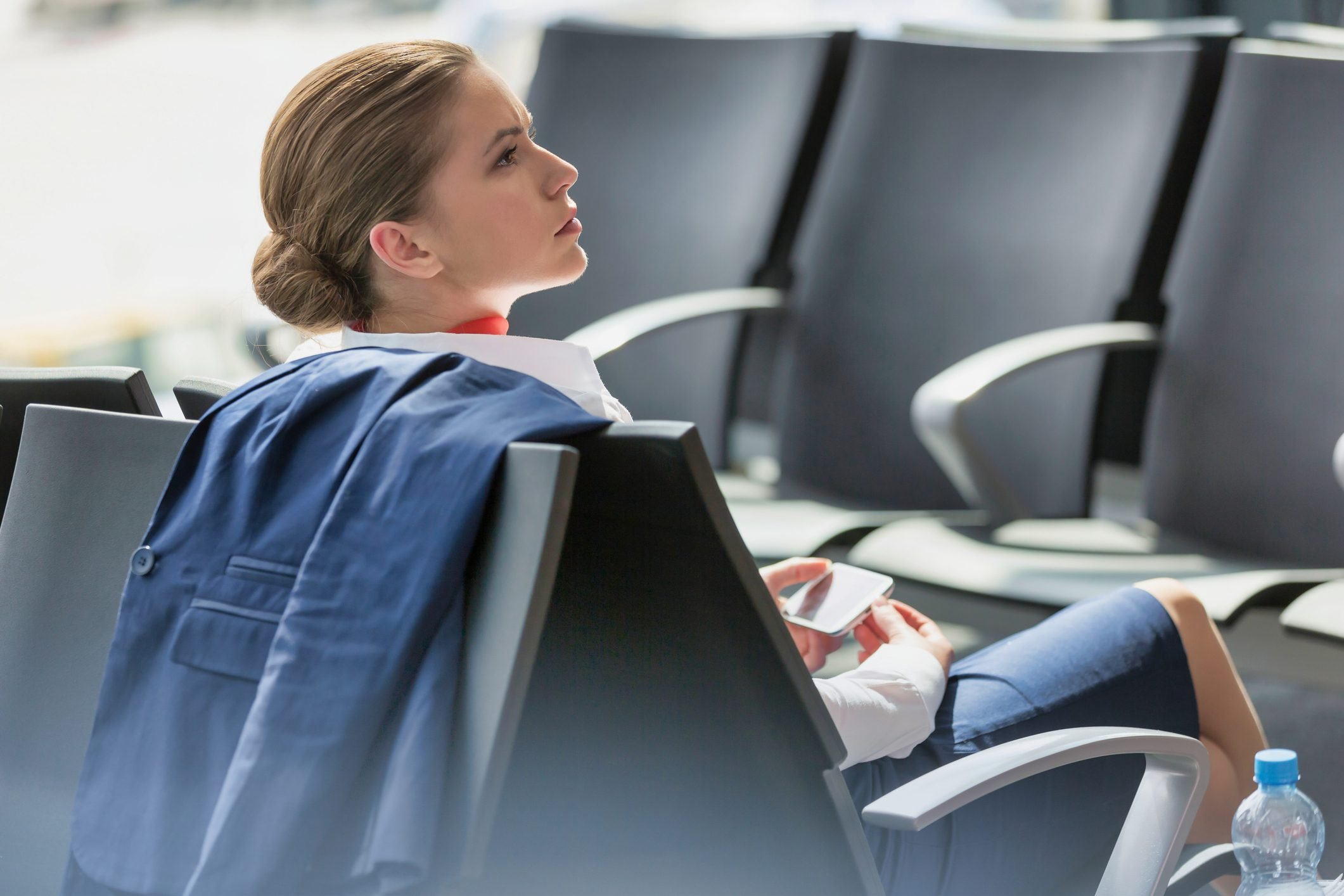 Young attractive businesswoman using smartphone while waiting for her flight in airport
