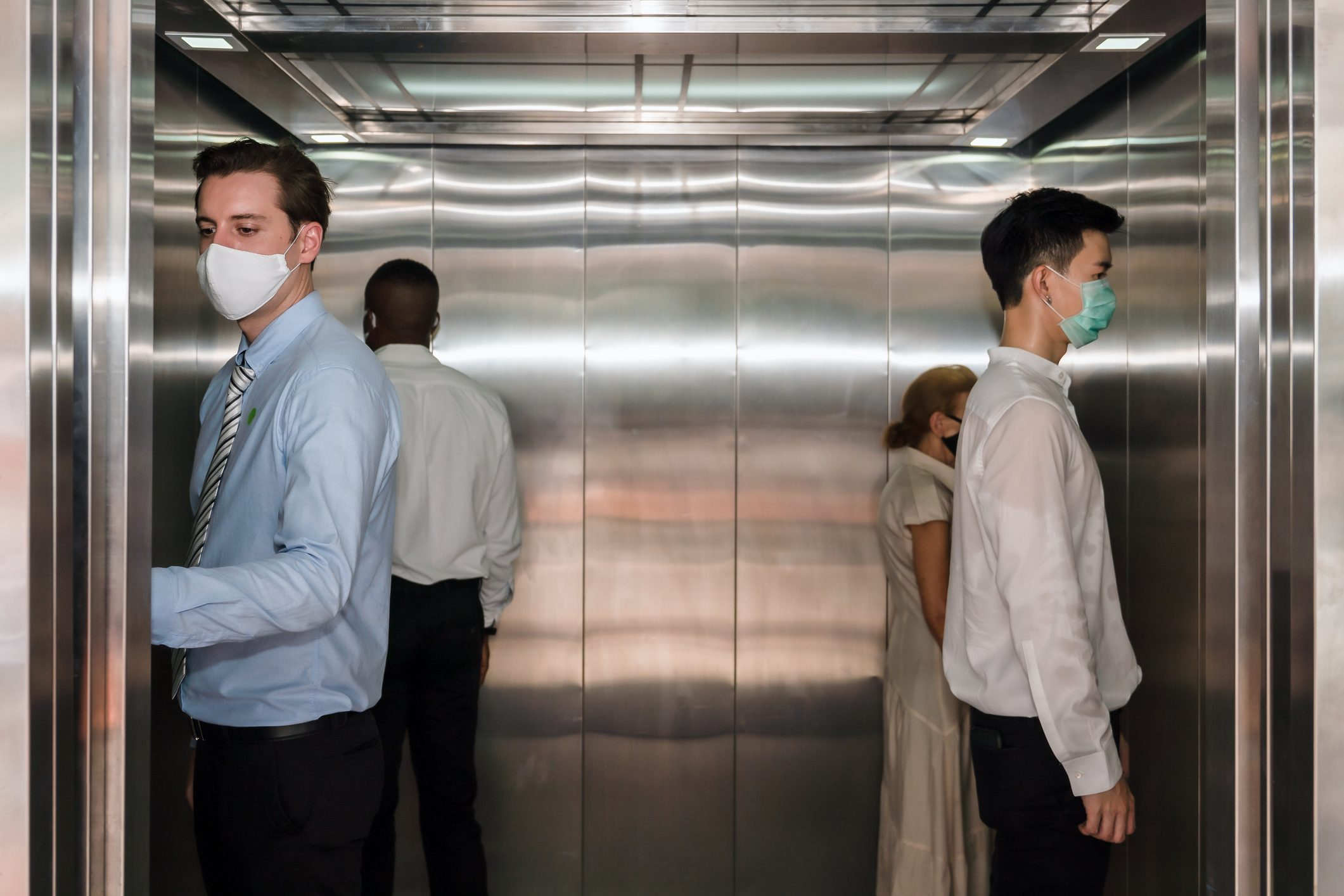 caucasian business man and other people standing apart from each in corner of elevator for social distancing to avoid coronavirus covid-19 spreading, selective focus