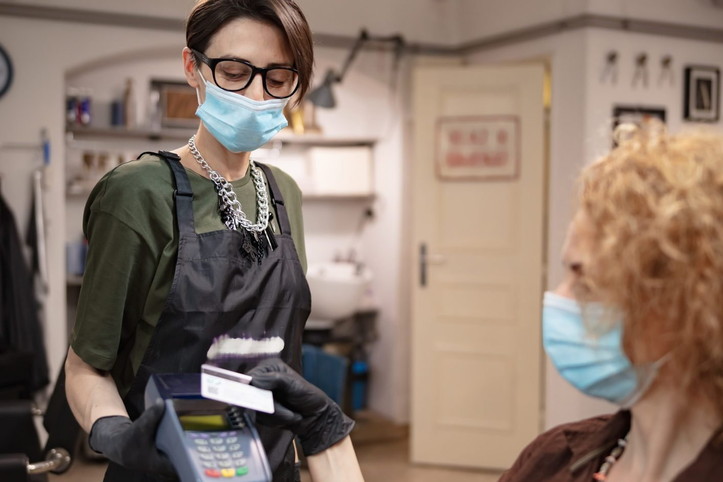 Paying with contactless card. Hairdresser and customer in a salon with medical masks during virus pandemic. Working with safety mask.