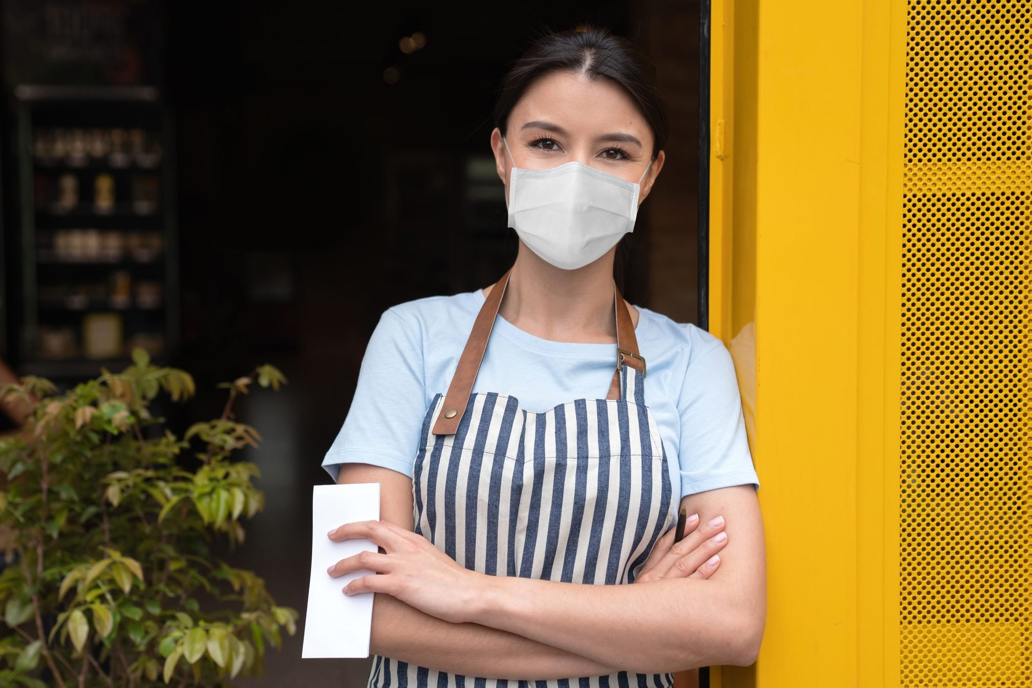 Business owner working at a cafe wearing a facemask