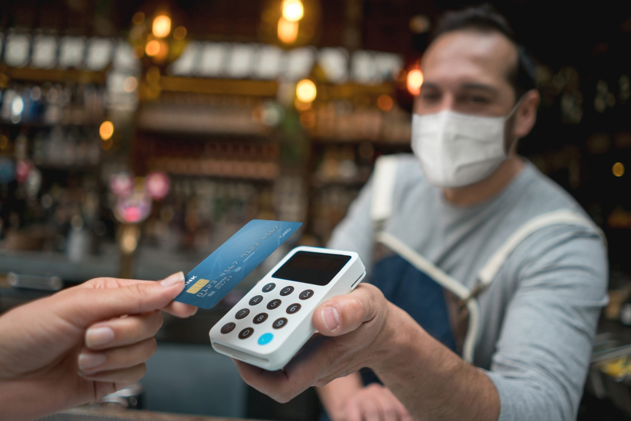 Waiter wearing a facemask while getting a contactless payment at a restaurant
