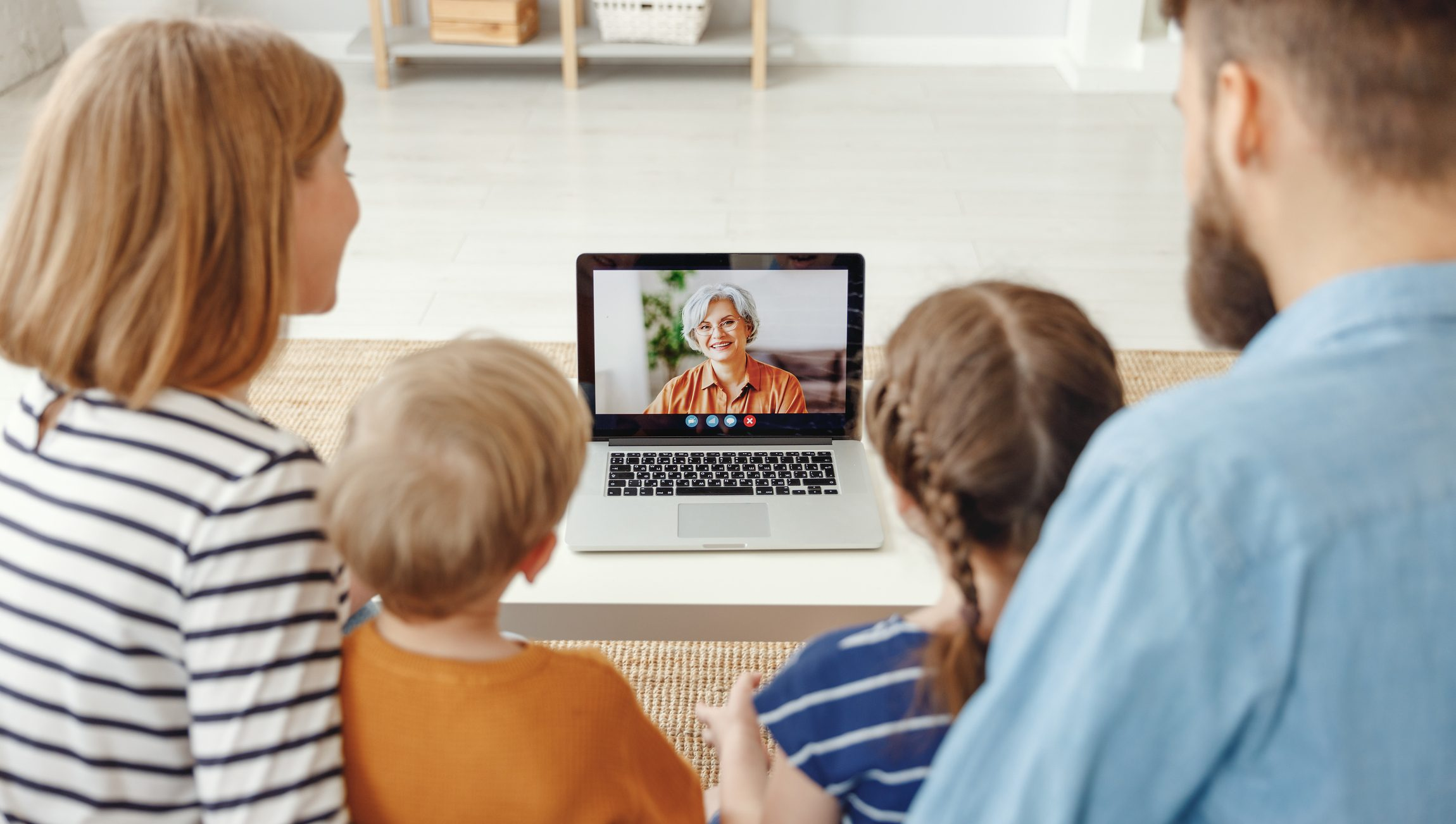 family talking to grandma on laptop video call