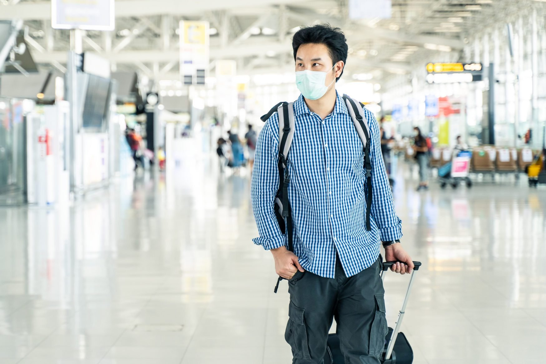 Asian traveler business man with luggage, bag wearing face mask looking time table in departure terminal in airport. Male passenger traveling by plane transportation during covid19 virus pandemic.