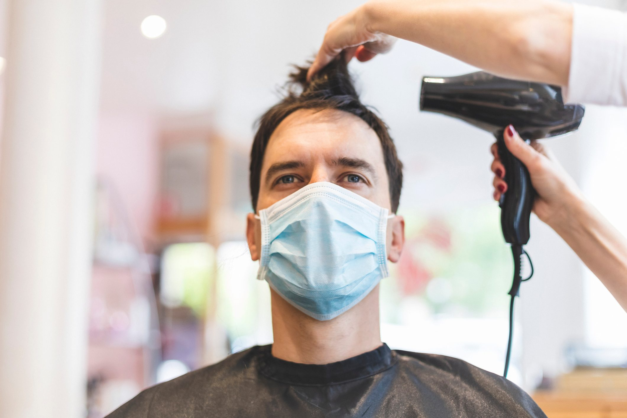 Hairdresser Drying Hair of Customer Wearing Protective Mask