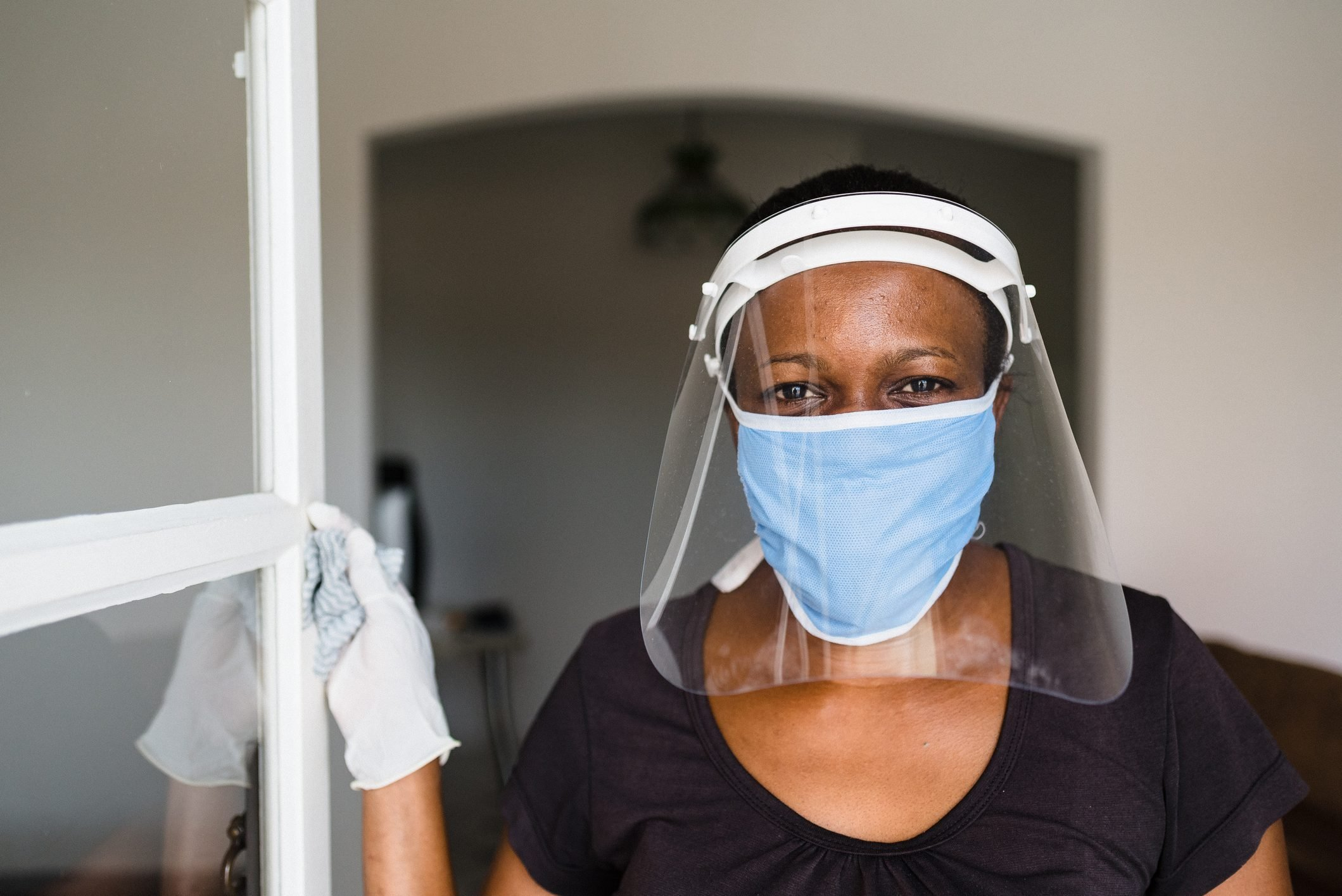 Covid-19: Portrait of a female worker wearing face shield and mask