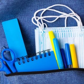 Blue backpack with different stationery and study supplies and medical face masks. Back to school concept. The concept of the teachers day. Protection against coronavirus of schoolchildren and students. Studying in the new reality pandemic.