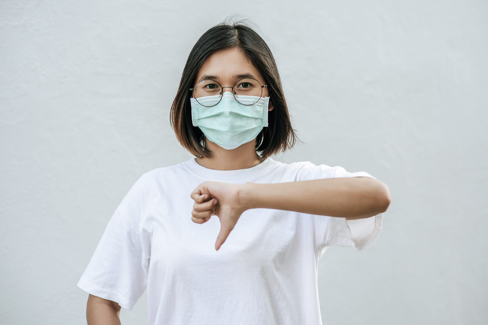 The woman is wearing a mask and pointing her thumb down.