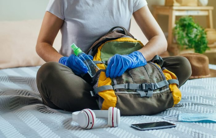 Close up of young woman packing her backpack with hand sanitizer in protective gloves