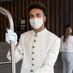 Happy bellboy working at a hotel and wearing a facemask to avoid COVID-19