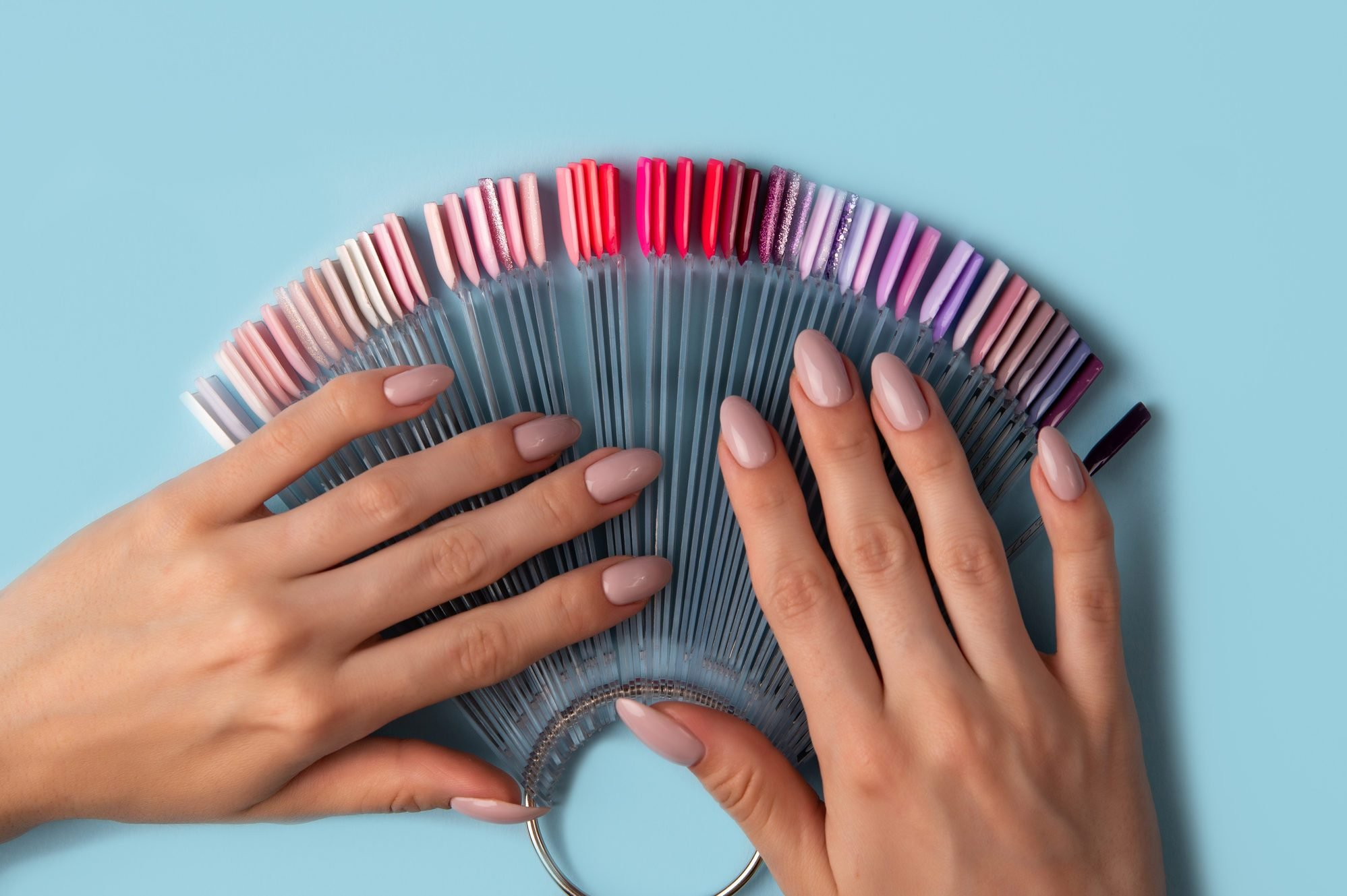 Woman holds in hands collection of color nail polish samples