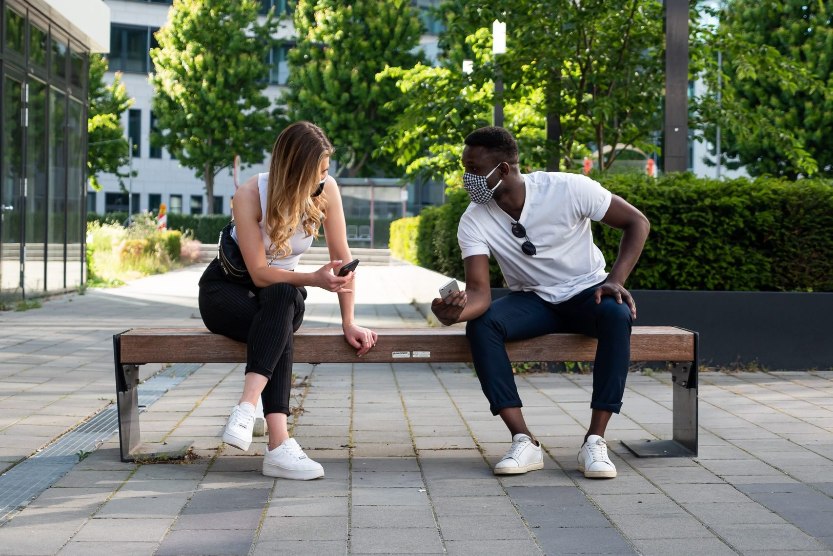 Young Man and Woman Social Distancing on Bench Using Phones