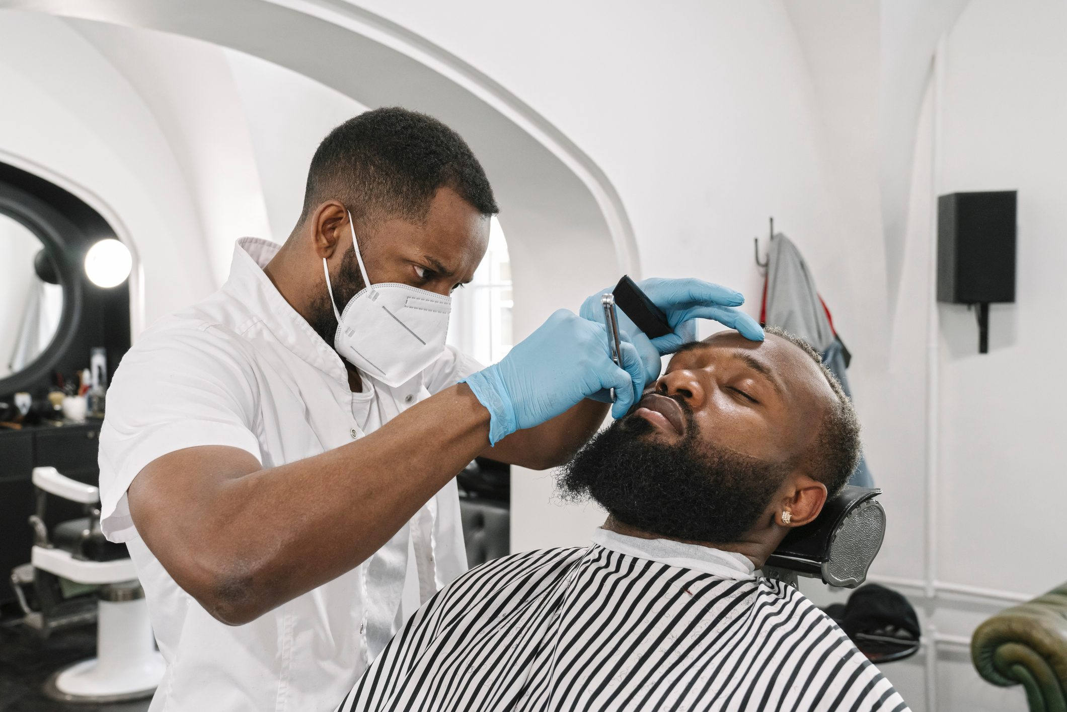 Man with full beard getting a shave, barber wearing surgical mask and gloves