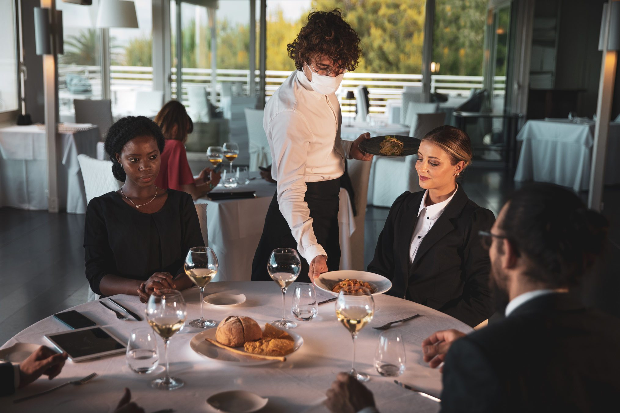 Waiter serving food in a luxury restaurant at a business people table