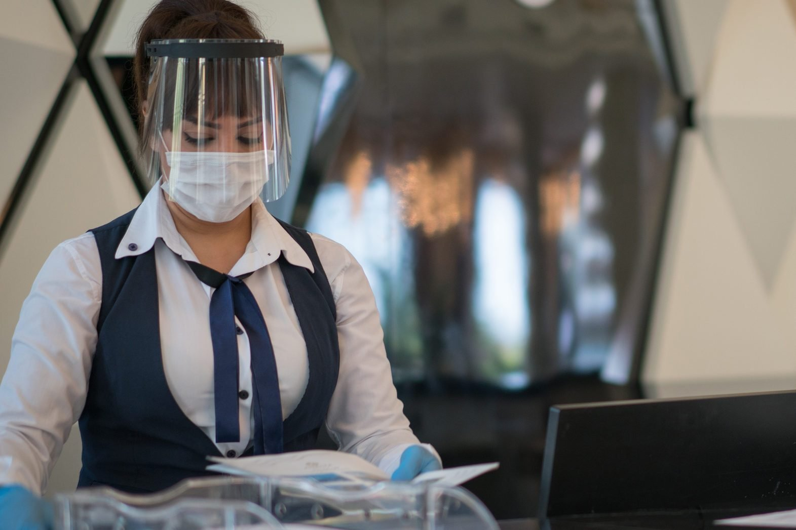 Receptionist lady welcomes her customer with protective face mask