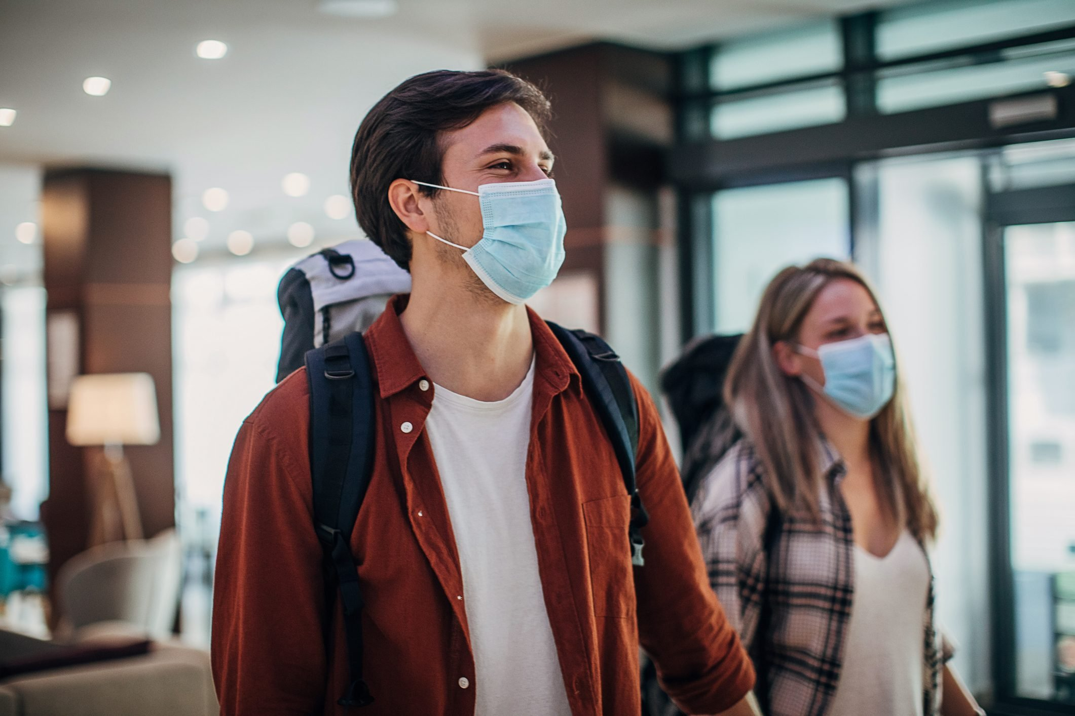 Couple travelers with medical masks just arrived in hotel