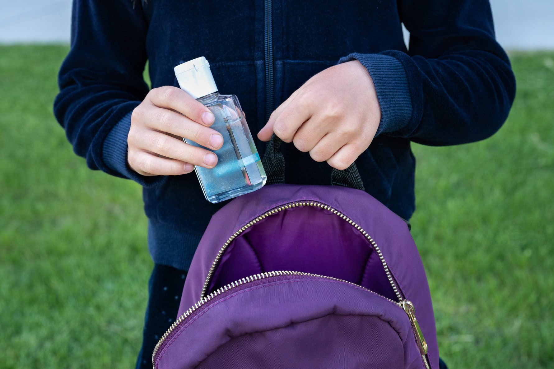 Putting hand sanitizer into backpack