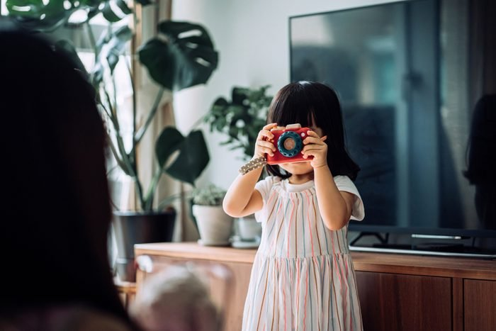 Cute little Asian girl with flower-shaped sunglasses acting like a professional photographer and taking photos of her mother and beloved soft toy with wooden toy camera at home