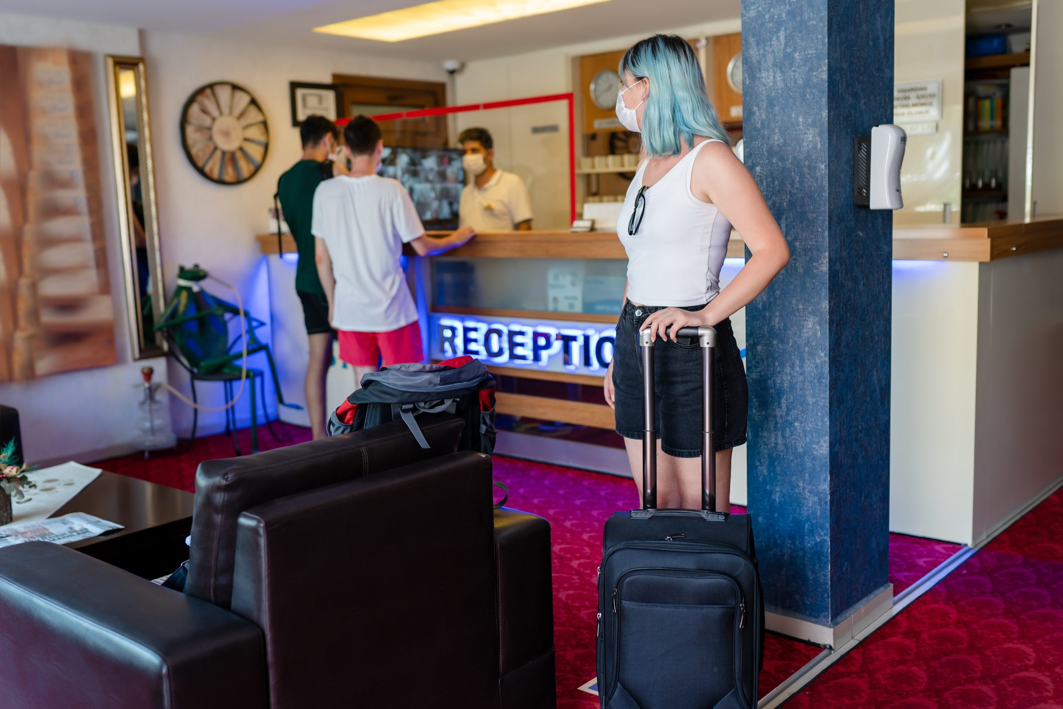 Millennial travelers on hotel reception talking to male receptionist