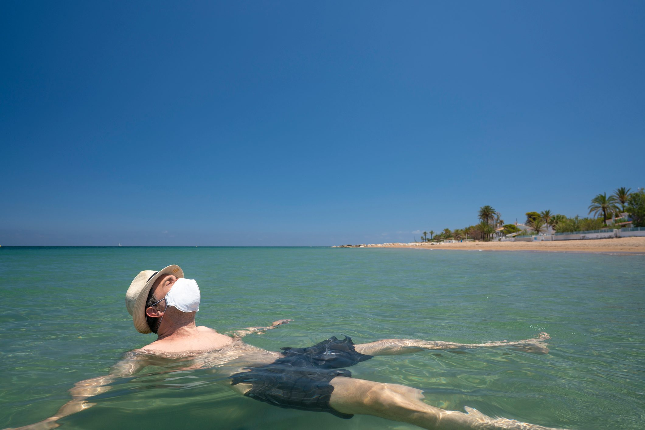 Adult turist man with N95 face mask in covid-19 on the beach