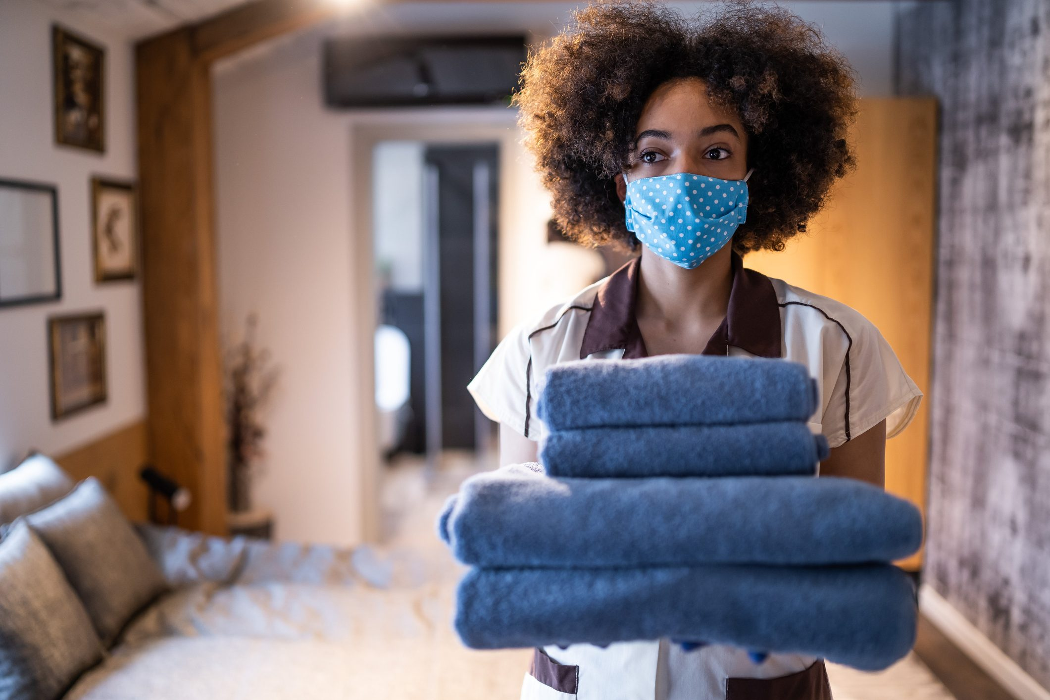 Maid working at a hotel wearing a protective face mask, during COVID-19