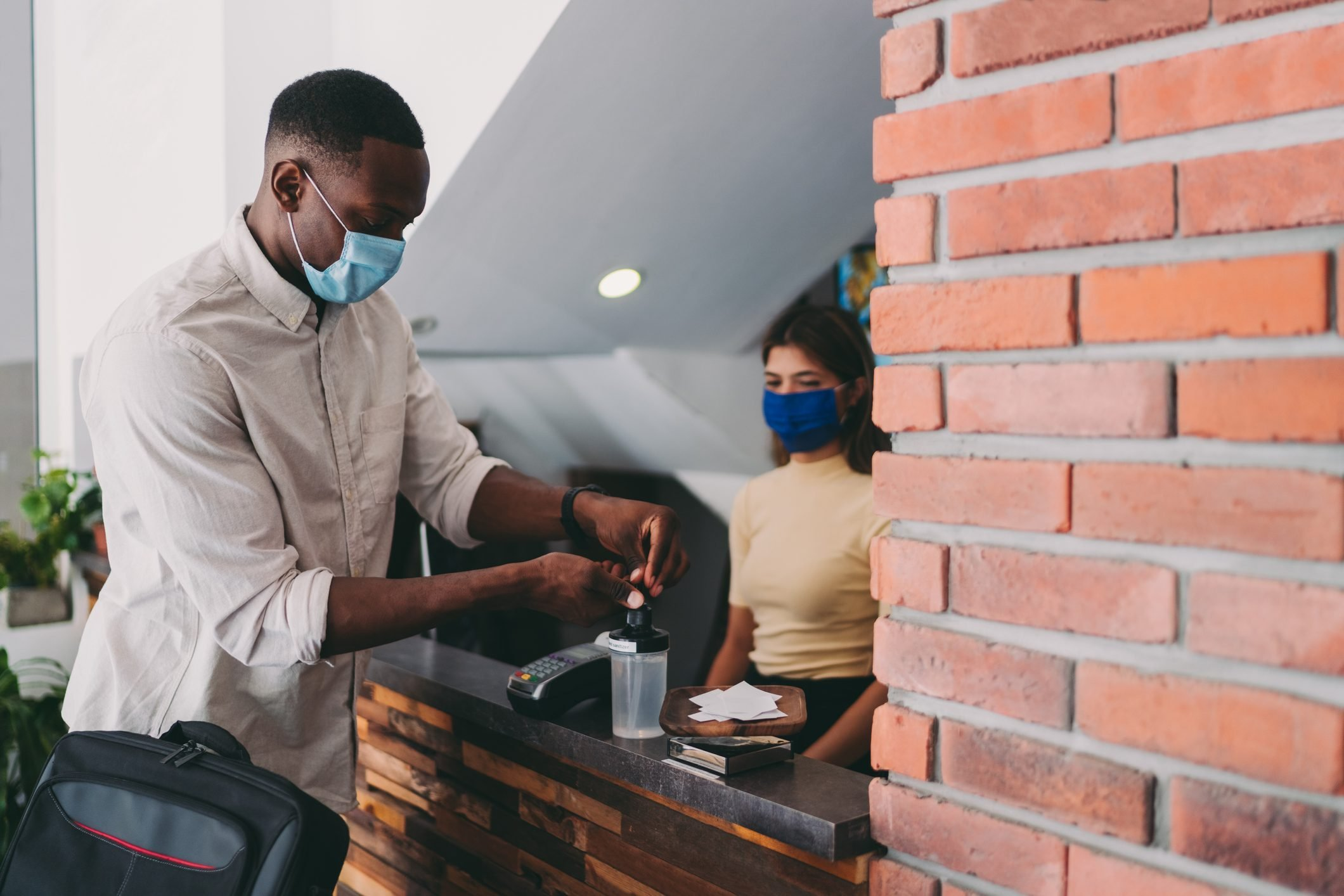 Businessman disinfecting his hands at hotel reception due to COVID-19 virus