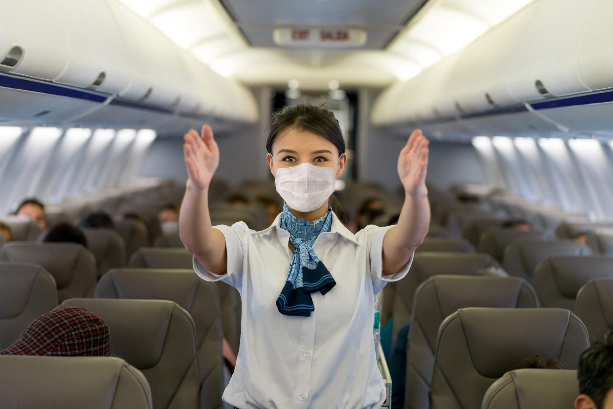 Flight attendant showing the emergency exit in an airplane wearing a facemask