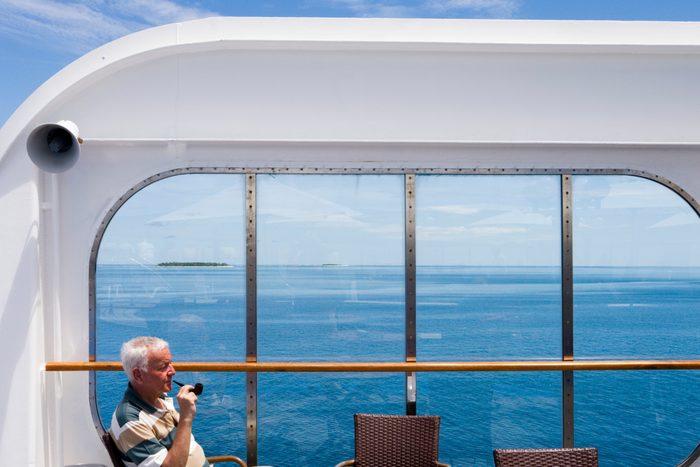 Man enjoys pipe aboard cruiseship MV Columbus (Hapag-Lloyd Cruises) during passage through islands of Mamanuca Group.