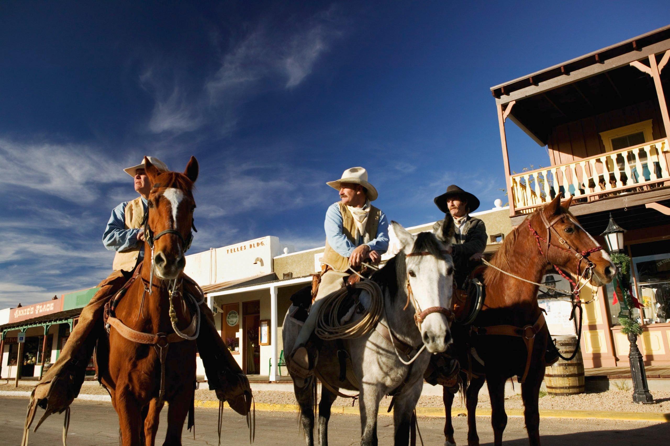 USA, Arizona, Tombstone, three cowboys on horseback
