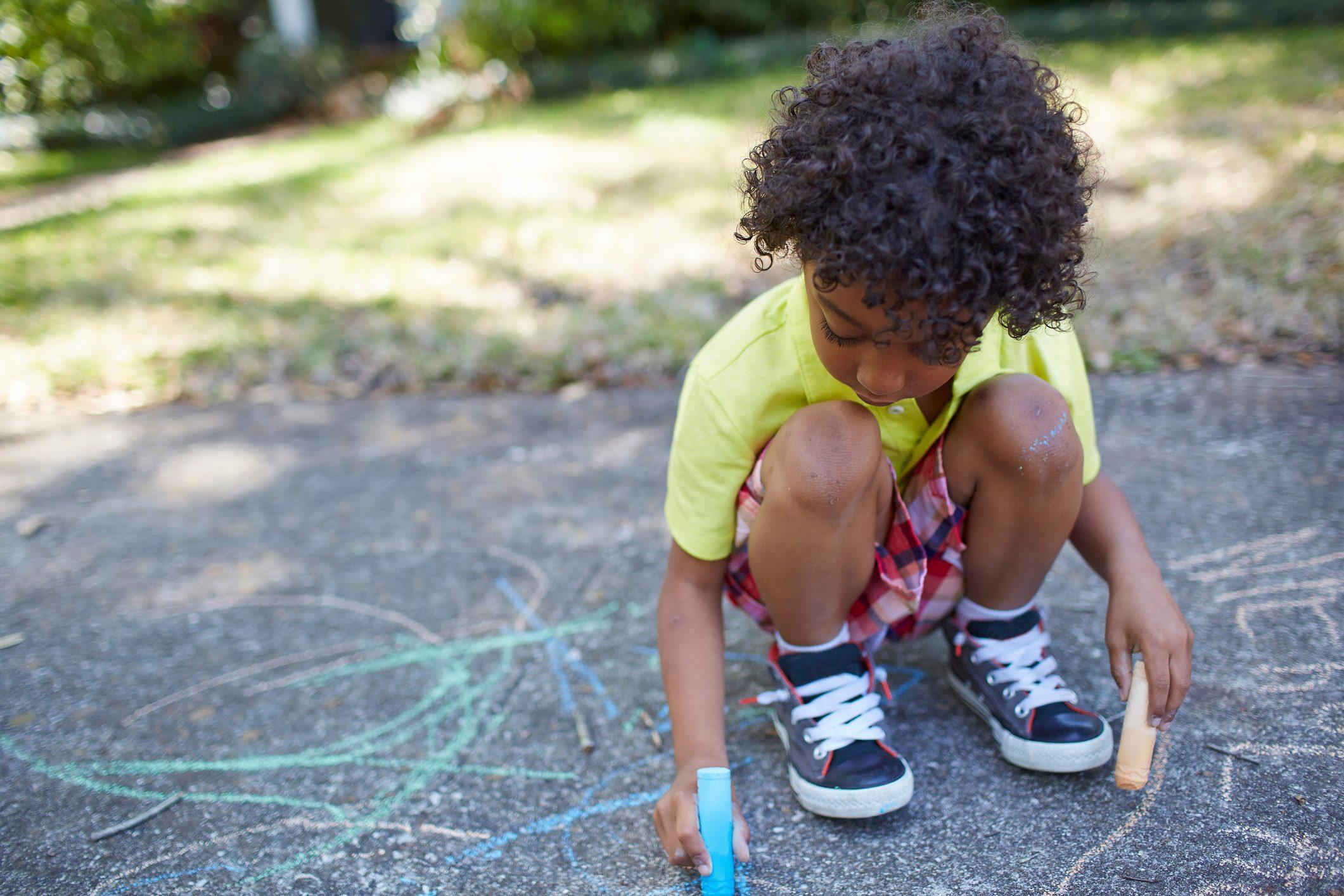 Boy drawing with chalk on sidewalk