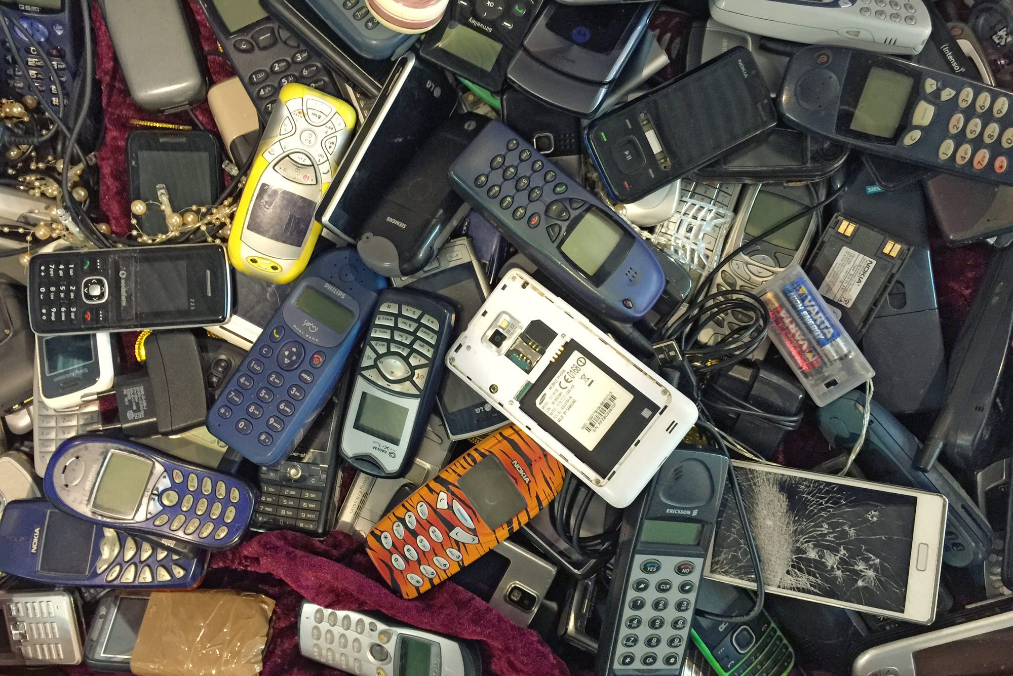 Pile of old, used and partly damaged mobile phones