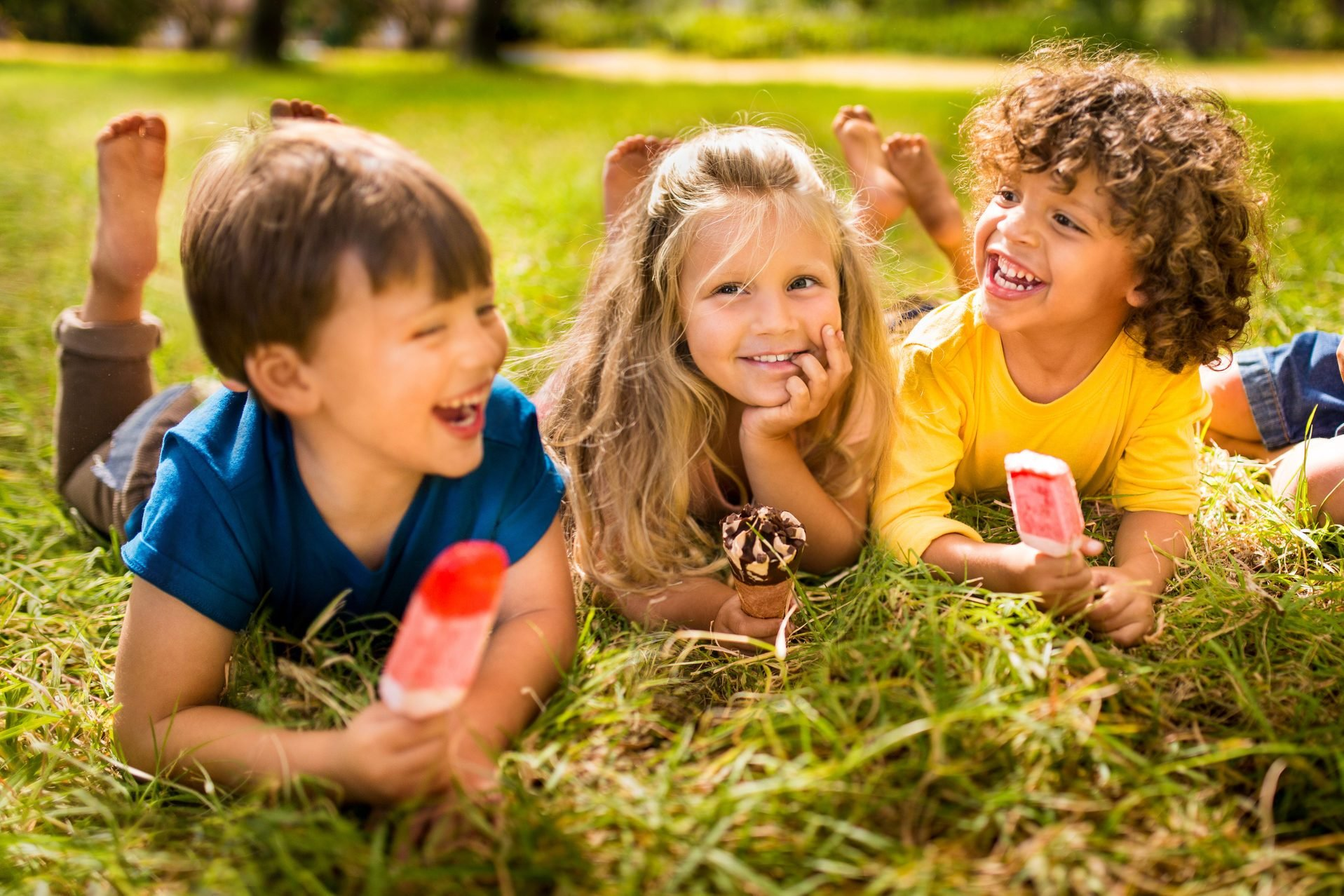 Children friends eating ice creams in park