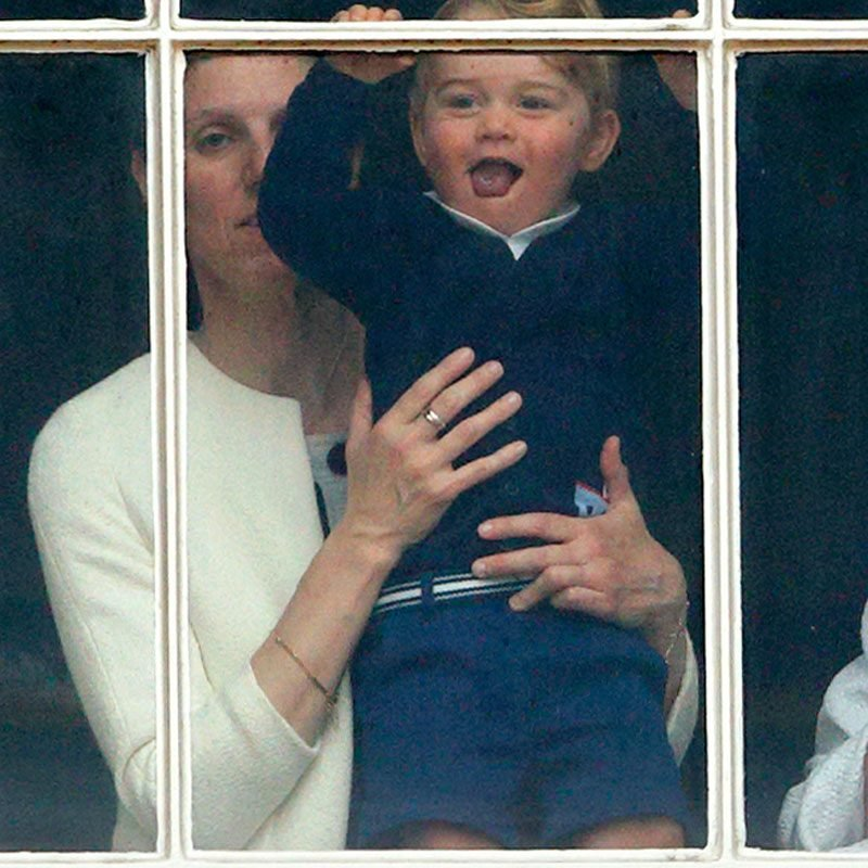 Prince George of Cambridge being held up at a window of Buckingham Palace by his nanny Maria Teresa Turrion Borrallo
