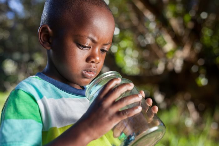 African child inspects bug in glass jar in his garden