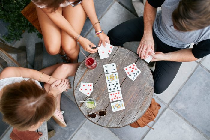 Young people playing cards at sidewalk cafe