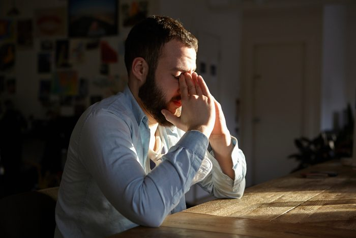 Young man sitting at kitchen table with hands on face