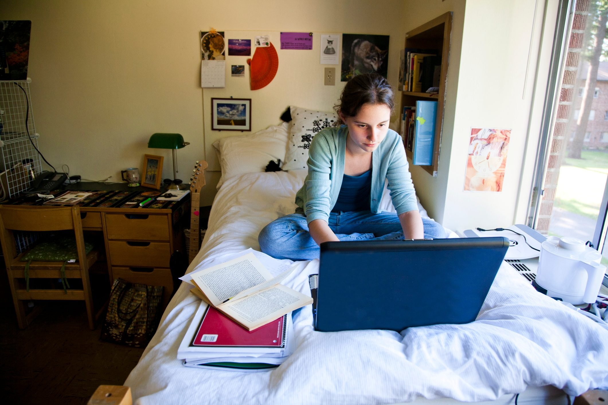 Female college student in her dorm room working on computer