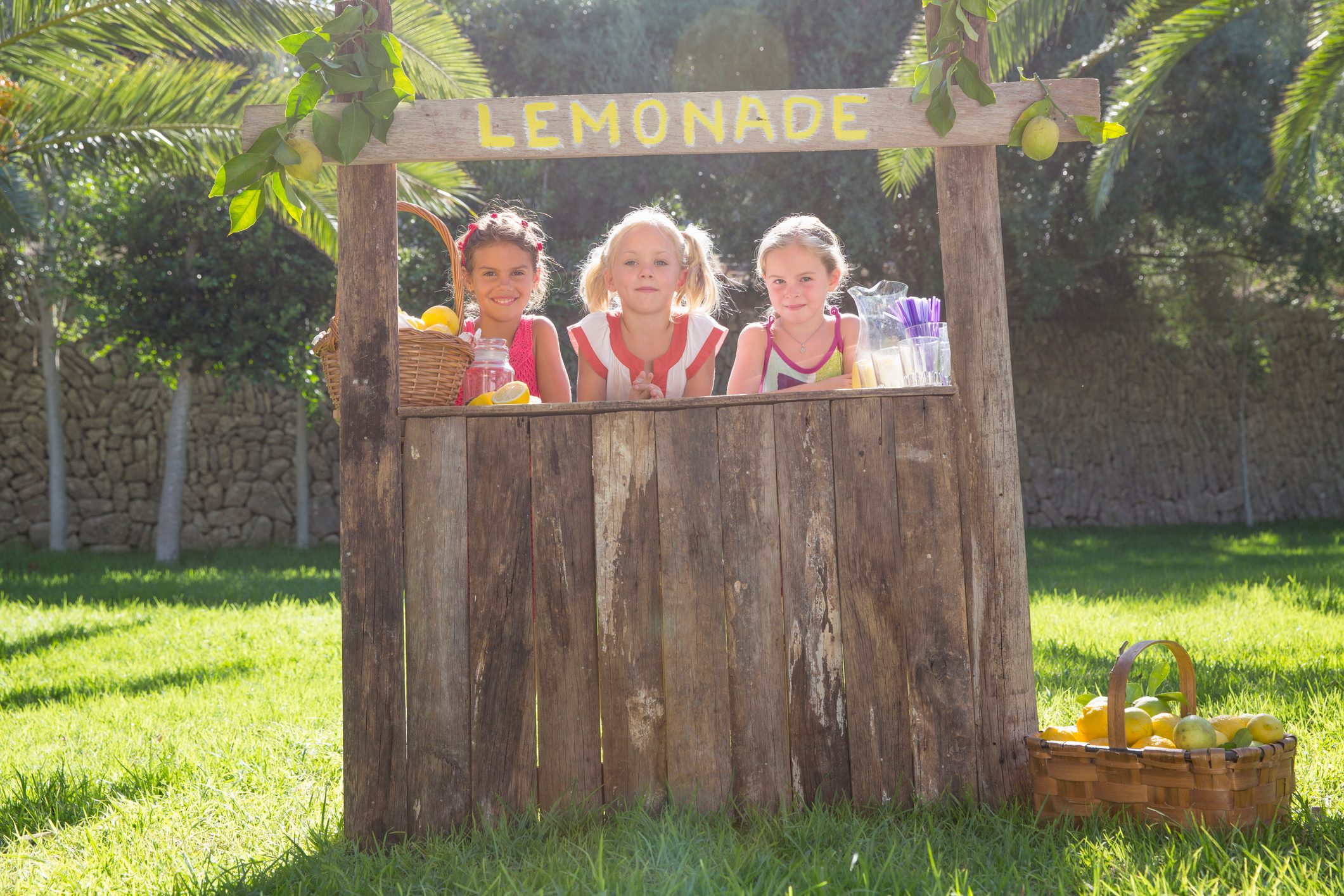 Portrait of three girls selling lemonade at stand in park