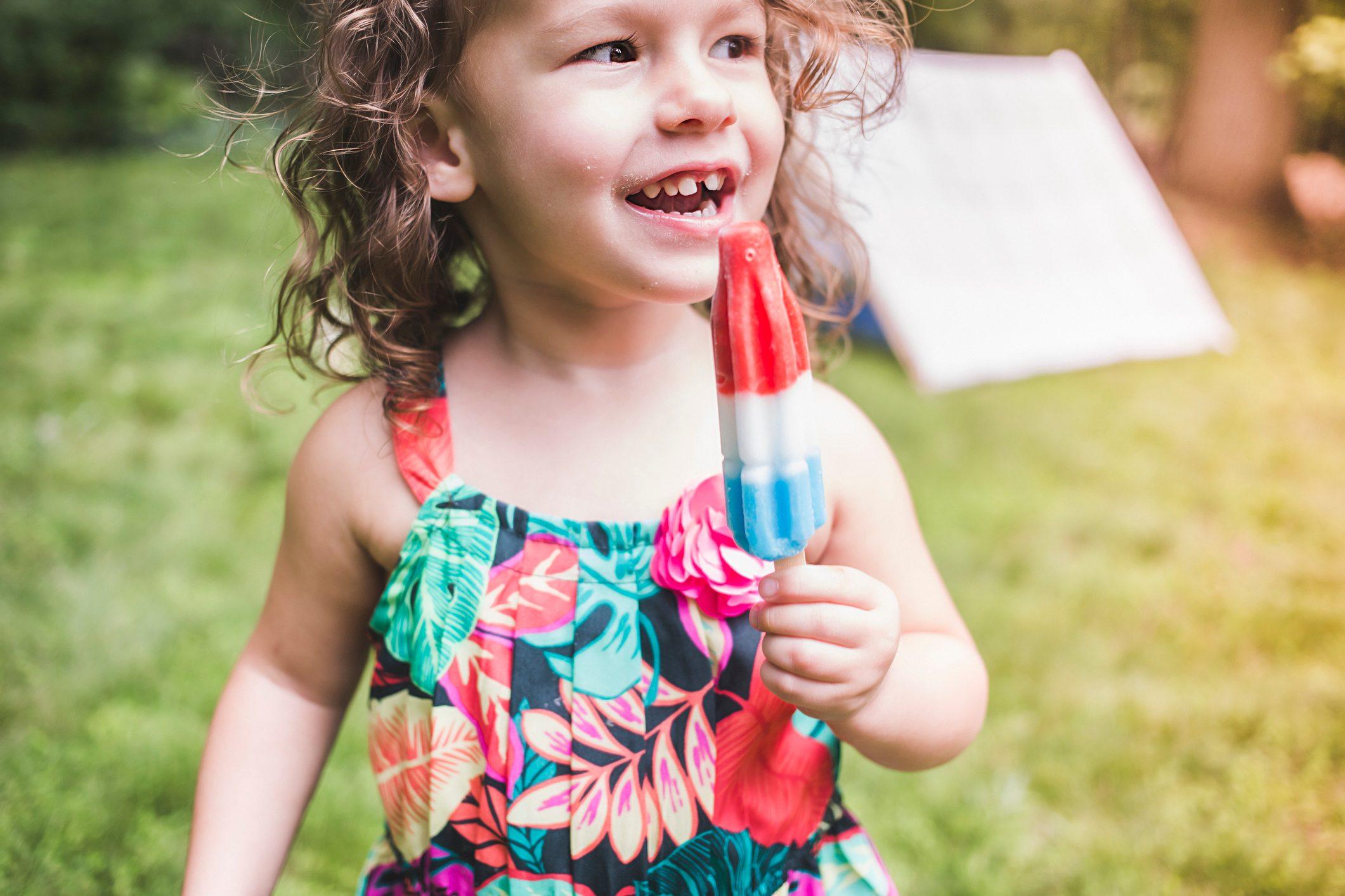 Girl in garden eating ice lolly