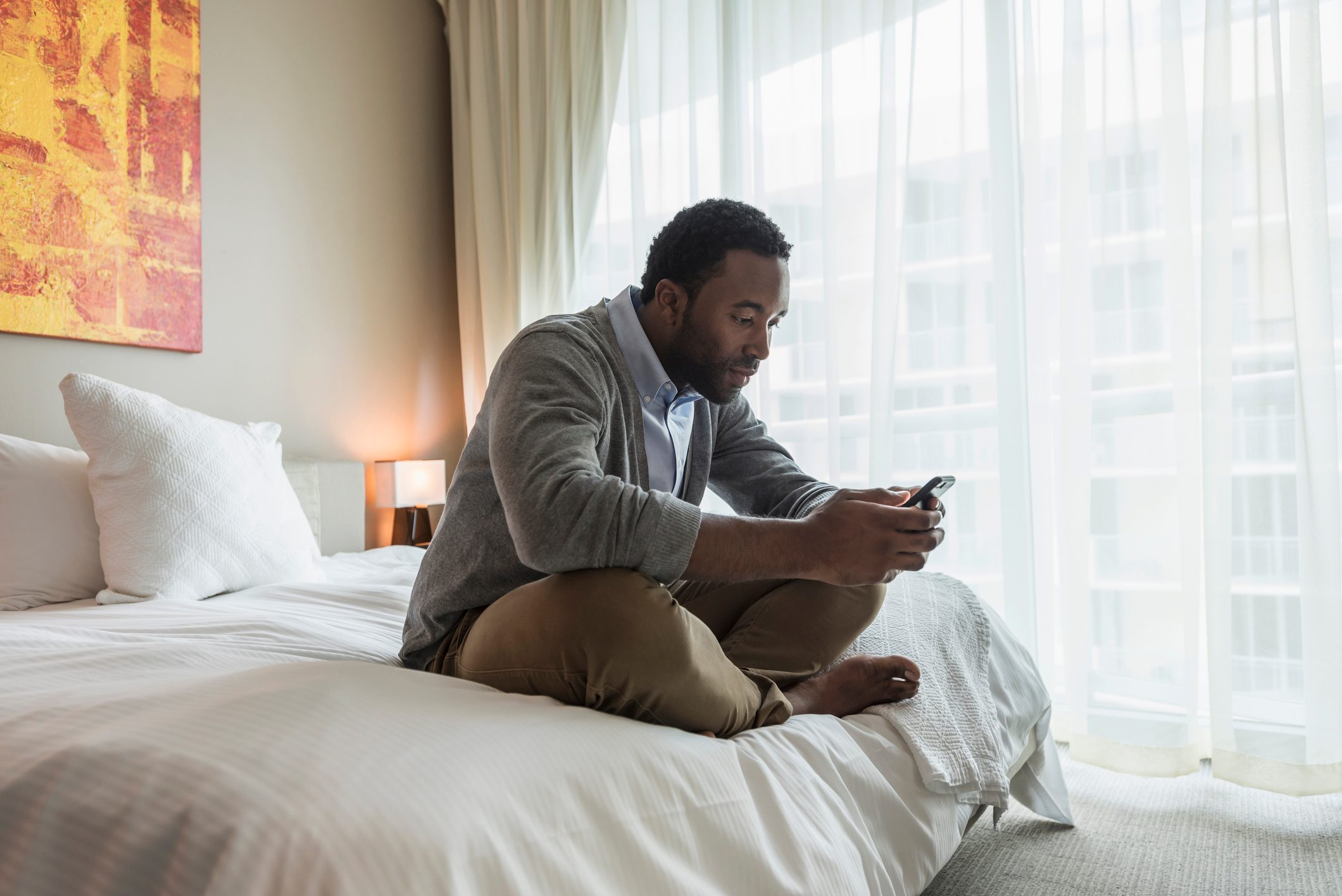 Black man using cell phone on bed