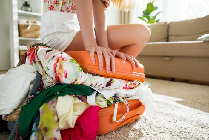 Girl packing overflowing suitcase for travel
